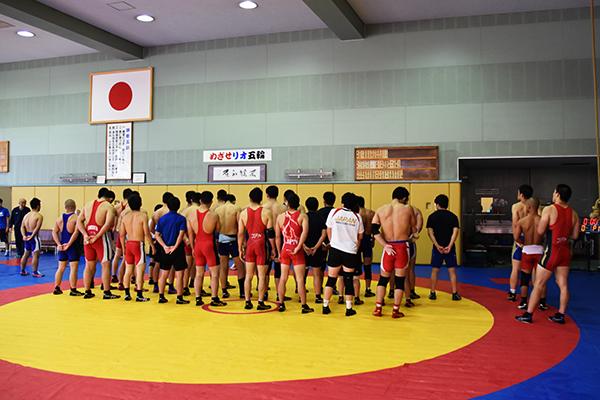 練習後、日の丸の下でコーチの話に耳をかたむけるレスリング選手たち