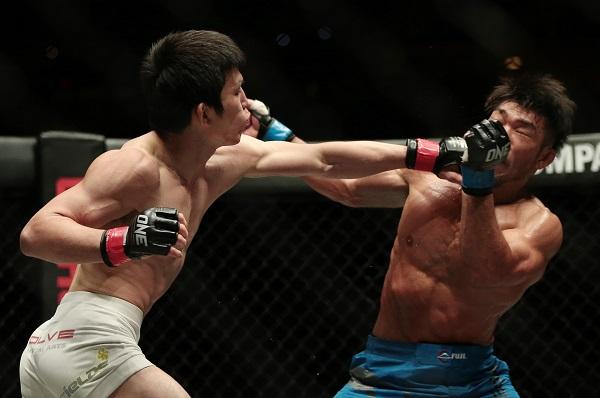 相手選手の顔面に拳を打ち込む青木(左)〈写真:Action Images/アフロ〉