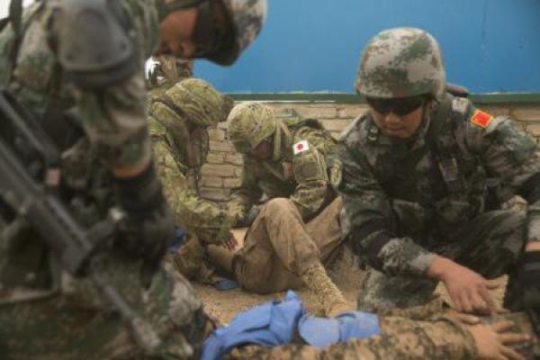 多国間演習カーンクエスト15で負傷者役のアメリカ海兵隊員に手当ての訓練をする陸上自衛隊と中国軍