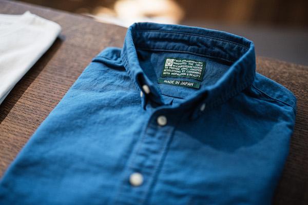"""""""フィールドマネージメント""""ブランドのシャツ。織りネームには、コーポレートカラーのグリーンベースにコーポレートロゴがあしらわれている。"""