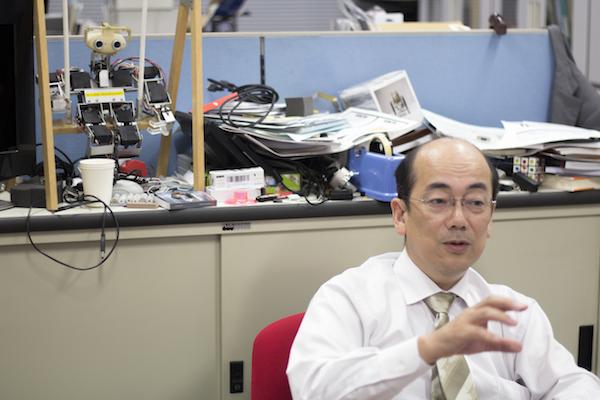 稲葉教授の後方、小型のヒューマノイドロボットがブランコに座っている